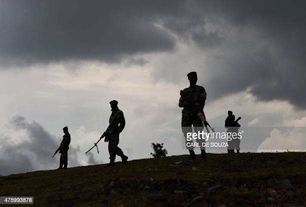 Soldiers stand guard near a house that was set on fire by protestors opposed to the Burundian president's bid to stand for a third term in Butagazwa...
