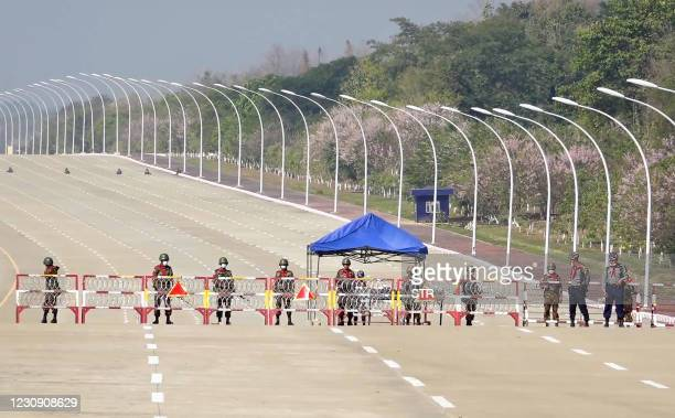 Soldiers stand guard on a blockaded road to Myanmar's parliament in Naypyidaw on February 1 after the military detained the country's de facto leader...
