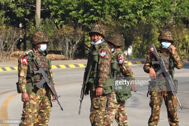 Soldiers stand guard on a street in Naypyidaw on February 1 after the military detained the country's de facto leader Aung San Suu Kyi and the...