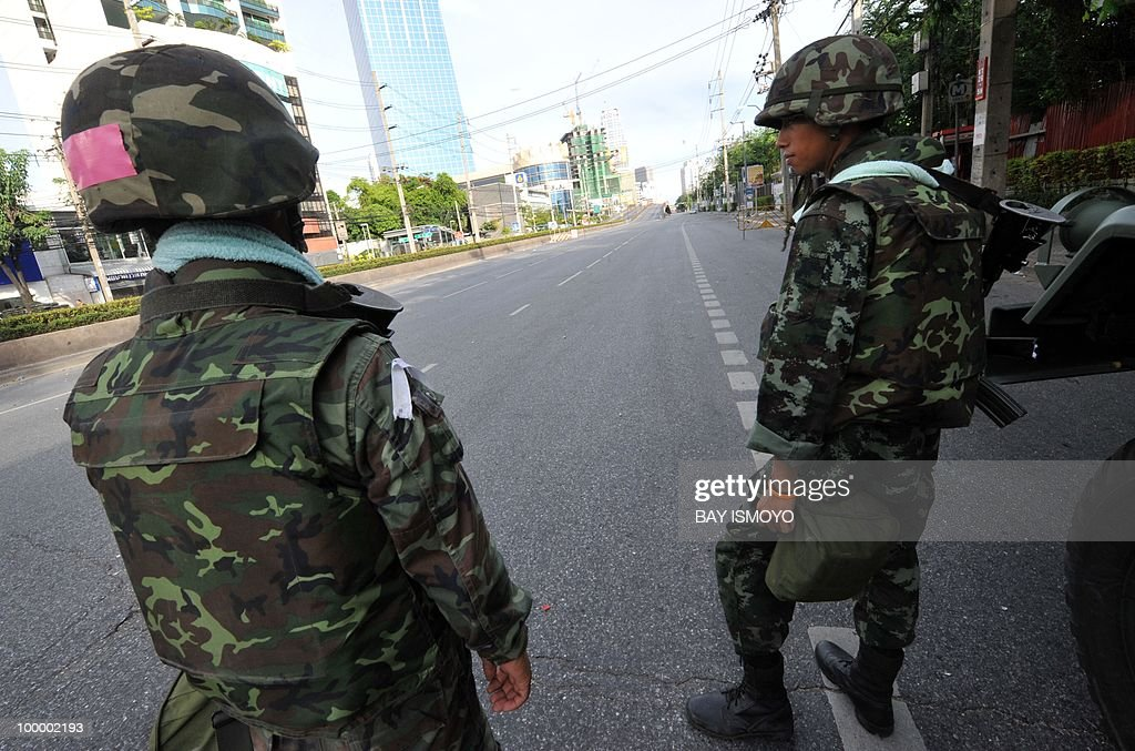 Soldiers stand guard on Rama IV boulevard in downtown Bangkok on May 20, 2010 where traces of burnt barricades and tyres remain. Plumes of smoke hung overhead as Bangkok emerged from an curfew aimed at quelling mayhem unleashed by enraged anti-government protesters targeted in an army offensive on May 2010.