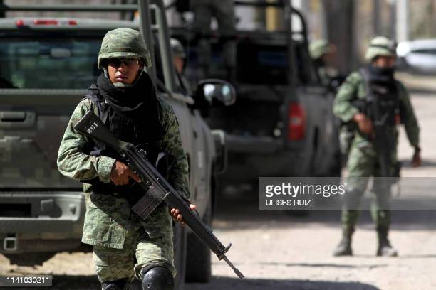 Soldiers stand guard outside a safe house where eight people with signs of torture were found alive along with four dead ones in Tlajomulco de Zuniga...