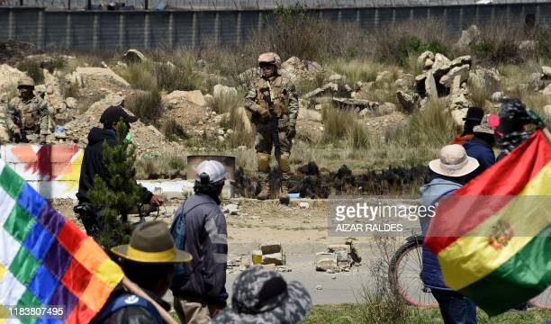 Soldiers stand guard outside the Senkata fuel plant during the funeral procession of eight supporters of Bolivia's ex-President Evo Morales, killed...