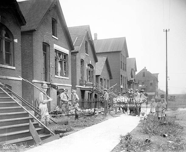 Soldiers stand guard with rifles at a house vandalized during the race riots of July-August 2, 1919 in Chicago, Illinois. A group of white adults and...