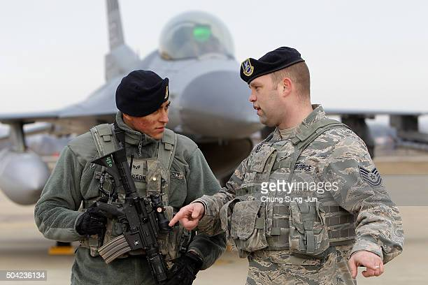 S soldiers stand guards in front of US F16 fighter jet at Osan Air Base on January 10 2016 in Pyeongtaek South Korea South Korea and the United...