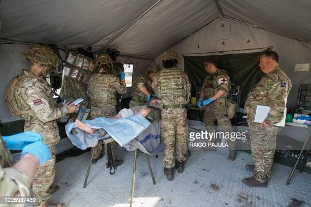 Soldiers stand in a tent around a person on a stretcher as they take part in a joint military exercise of British, Estonian and Danish forces at the...