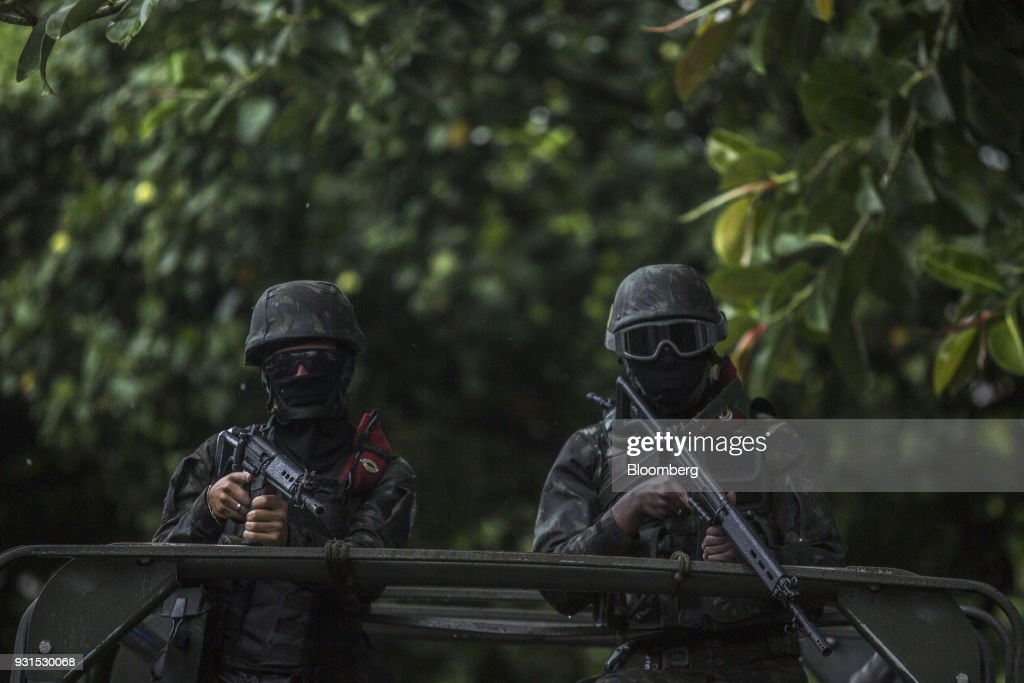 Soldiers stand in a vehicle while patrolling streets in the Vila Kennedy neighborhood in Rio de Janeiro, Brazil, on Thursday, March 8, 2018. As public safety remains a top concern for Brazilian voters, President Michel Temer gave the military control of security measures in Rio in an effort increase approval ratings ahead of the country's elections in October. Photographer: Dado Galdieri/Bloomberg via Getty Images