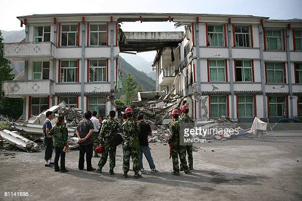 Soldiers stand in front of a collapsed school in Hongkou township on May 18 2008 in Dujiangyan Sichuan province China A major earthquake measuring 79...
