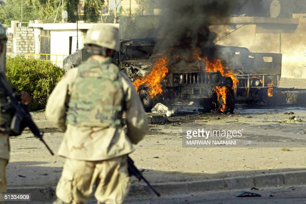 US soldiers stand in front of two burning US Humvees at the site of a suicide car bomb attack 22 September 2004 in Baghdad's alMansur area Another...