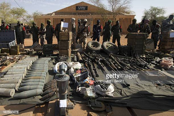 Soldiers stand in front of weapons and ammunitions seized from Islamist fighters exhibited by the Malian army in the centre of Gao on February 24,...