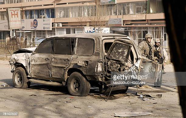 US soldiers stand near a damaged car at the site of a suicide attack in Kabul 27 November 2007 A suicide car bomb aimed at USled coalition soldiers...
