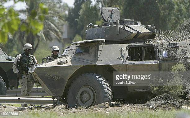S soldiers stand near a Striker armored vehicle that was hit by a roadside attack June 5 2004 in Baghdad Iraq One soldier was killed and three more...