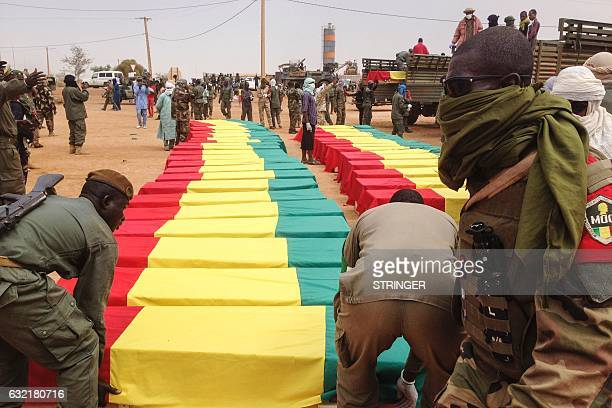 Soldiers stand near caskets at a funeral ceremony for victims of January 18 suicide bomb attack that ripped through a camp grouping former rebels and...