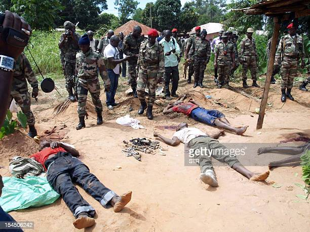 Soldiers stand next to dead bodies after gunmen raided a GuineaBissau army barracks sparking a firefight that left at least seven people dead in the...