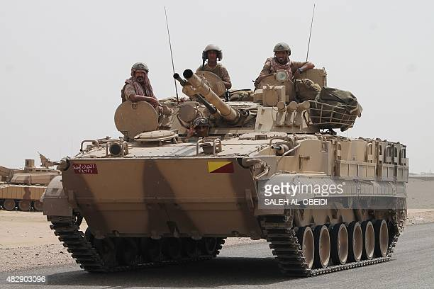 Soldiers stand on a tank of the Saudiled coalition deployed on the outskirts of the southern Yemeni port city of Aden on August 3 during a military...