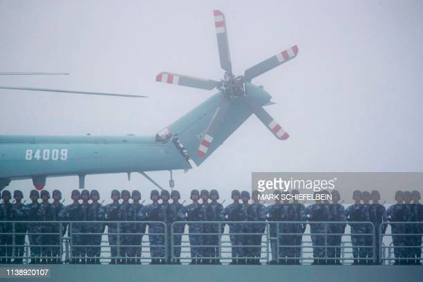 Soldiers stand on deck of the ambitious transport dock Yimen Shan of the Chinese People's Liberation Army Navy as it participates in a naval parade...