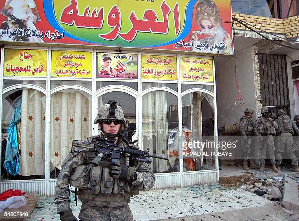 US soldiers stand outside a bridle shop close to the scene of a road side bomb which damaged a mini bus carrying Shiite Muslims going to visit the...