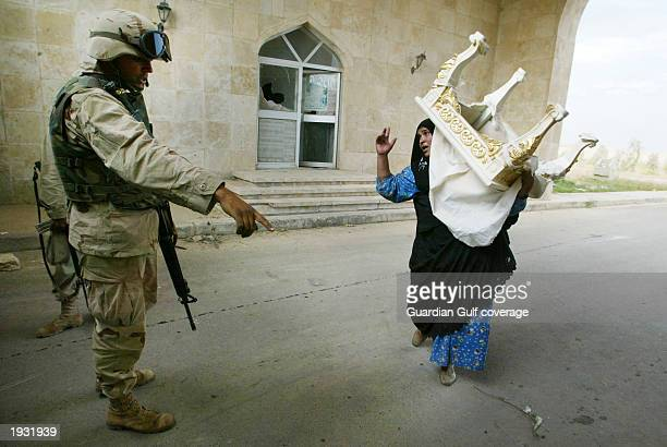 US soldiers stand outside Saddam Hussein's palace while local residents loot the place April 14 2003 in Tikrit Iraq US troops moved through the...