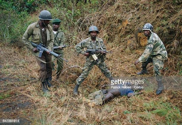 AFL soldiers stand over the body of a young man killed during the Liberian Civil War AFL forces under pressure from Ghanaian ECOMOG forces are...
