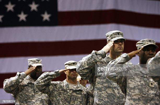 Soldiers stand saluting during the national anthem for the redeployment ceremony at Marshall Army Air Field inside hanger 727 for the 1st Battalion...