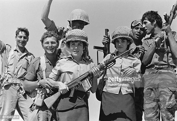 Soldiers stand with two women one of whom is holding a rifle during part of the SixDay War between Israel and Egypt