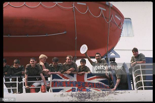 Soldiers standing under raised lifeboat on deck of QE2 before sailing for Falklands