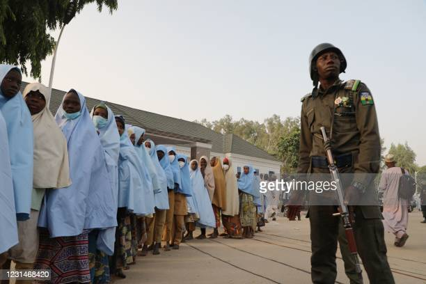 Soldiers stands next to a group of girls previously kidnapped from their boarding school in northern Nigeria are seen on March 2, 2021 at the...
