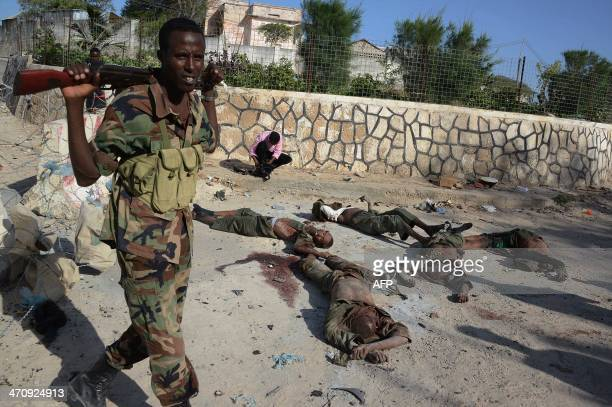 Soldiers stands next to the bodies of seven Al Shebab rebels in front the presidential palace on February 21 2014 in Mogadishu At least 14 people...