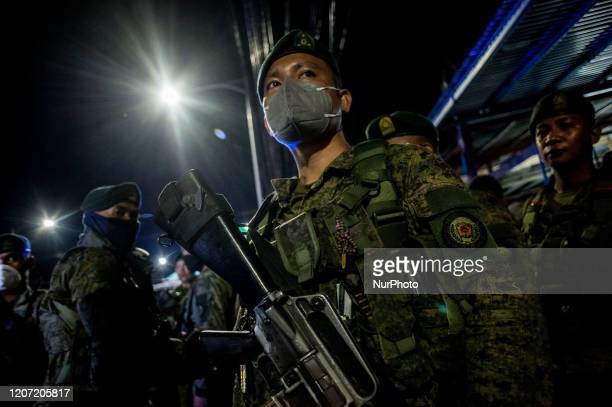 Soldiers stay at a checkpoint along a major thoroughfare in Valenzuela City, Philippines following the implementation of community quarantine in the...