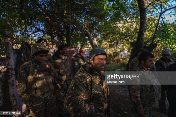 Soldiers stay under the cover of trees as a Azerbaijan drone flies occasionally flies overhead near Hadrut, Nagorno-Karabakh, which is also...