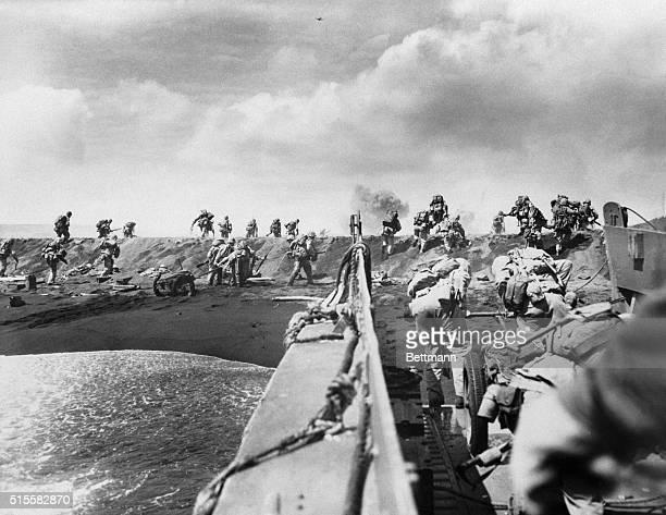 Soldiers storm a beach on Iwo Jima during the Battle of Iwo Jima.