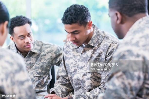 soldiers support friend with ptsd - soldier praying stock photos and pictures
