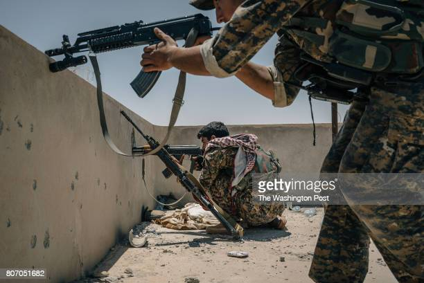 SDF soldiers take aim at a minaret where they believe an IS sniper is positioned on the western edge of Raqqa city