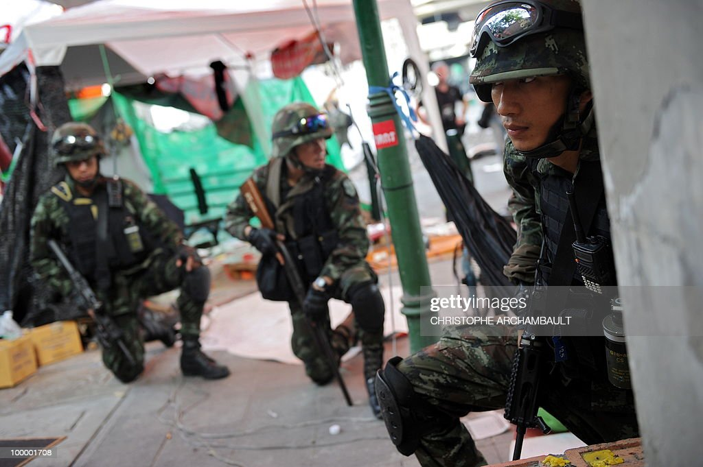 Soldiers take cover after gun shots rang out near a Buddhist temple in the heart of an anti-government protest zone, in downtown Bangkok on May 20, 2010. Gunshots rang out near a Buddhist temple in the heart of an anti-government protest zone in Bangkok, and soldiers were advancing on foot along an elevated train track, an AFP photographer saw. Thai security forces stormed the 'Red Shirts' protest camp on May 19 in a bloody assault that forced the surrender of the movement's leaders who asked their supporters to disperse. AFP PHOTO/Christophe ARCHAMBAULT