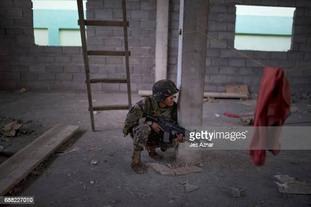 Soldiers take positions while evading sniper fire as they try to clear the city of armed militants one street at a time on May 25 2017 in Marawi city...