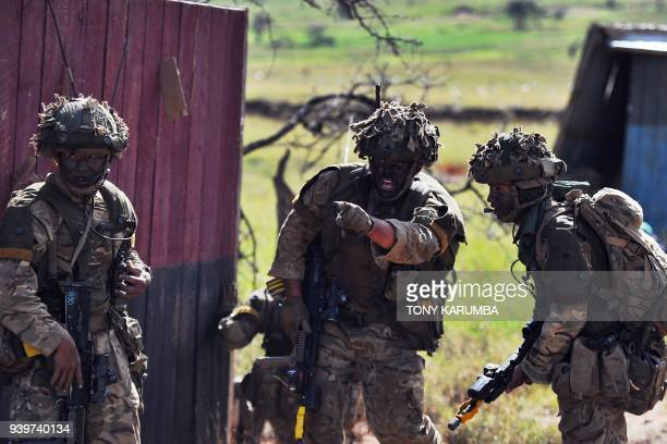 Soldiers take up position prior to an offensive on a mock insurgent training camp during a simulated military excercise of the British Army Training...