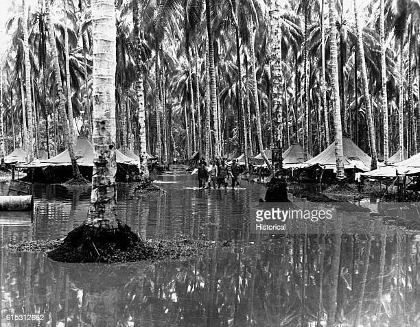 Soldiers traipse through the water at a Marine camp following a rainstorm on Guadalcanal Island during World War II. The Battle of Guadalcanal...