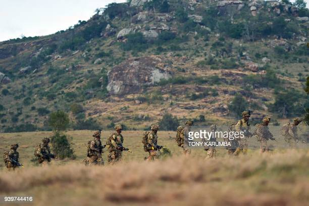 Soldiers troop during a simulated military excercise of the British Army Training Unit in Kenya together with the Kenya Defence Forces at the olDaiga...