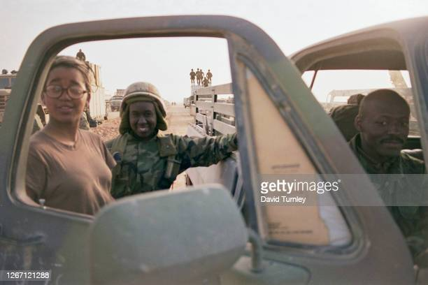 Soldiers, two dressed in military fatigues, pose beside the open door of a truck, in the Saudi–Iraqi neutral zone on the border between Saudi Arabia...