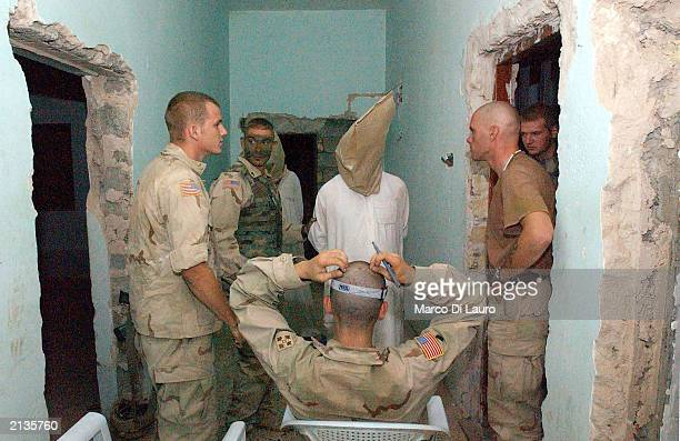 S soldiers undertake initial interrogation of a prisoner accused of being a senior officer of the Secret Security Police of the Baath Party after a...