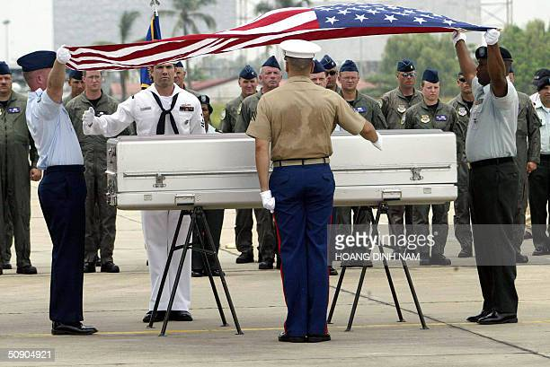 US soldiers unfold an American flag to cover a casket containing what is believed to be the remains of a US serviceman killed during the Vietnam War...