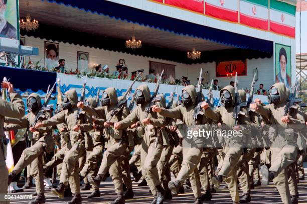 A soldiers unit wearing antichemical weapons suits parades on September 24 1995 in front of Iranian President Ali Akbar HashemiRafsandjani and...