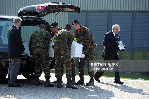Soldiers unload the coffin of a victim from a hearse on March 21 2012 at the Soeverein Arena in the northern Belgian town of Lommel before the...