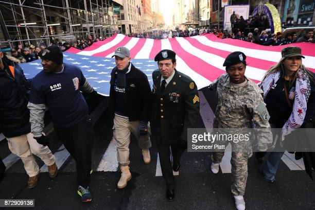 Soldiers veterans and civilians carry an American Flag as they march in the Veterans Day Parade on November 11 2017 in New York City The largest...