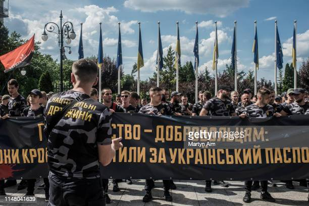 Soldiers, veterans and supporters of Azov Battalion hold a banner that reads, 'Citizenship for Volunteers - they have paid for it with their blood'...