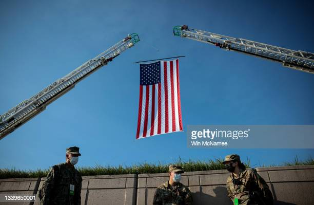 Soldiers wait below an American Flag prior to the start of the Pentagon 9/11 observance ceremony at the National 9/11 Pentagon Memorial on September...