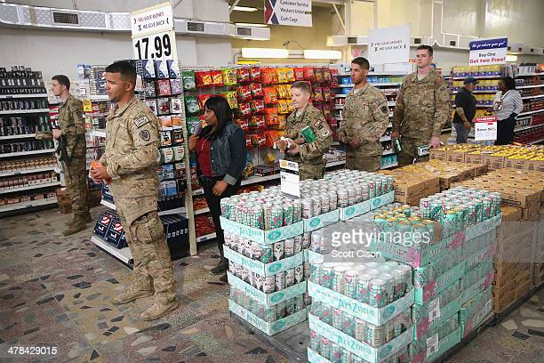 Soldiers wait in line to make purchases at the post exchange on Bagram Airfield on March 13, 2014 near Bagram, Afghanistan. Located about 35 miles...