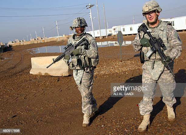 US soldiers walk at the Taji base complex which hosts Iraqi and US troops and is located thirty kilometres north of the capital Baghdad on December...