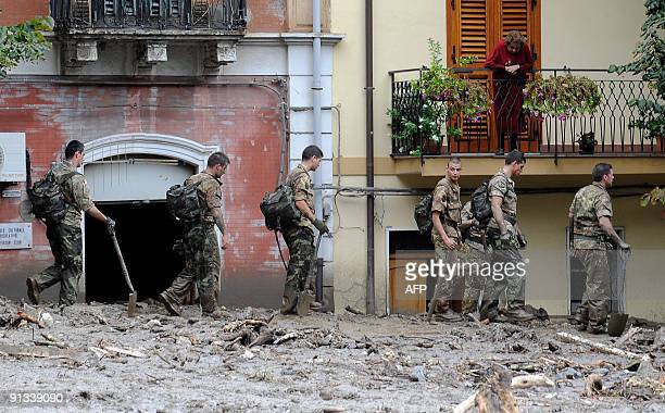 Soldiers walk in a flooded street as a woman looks down from a balcony next to collapsed houses in Gianpilieri on October 2 2009 Rescue workers and...