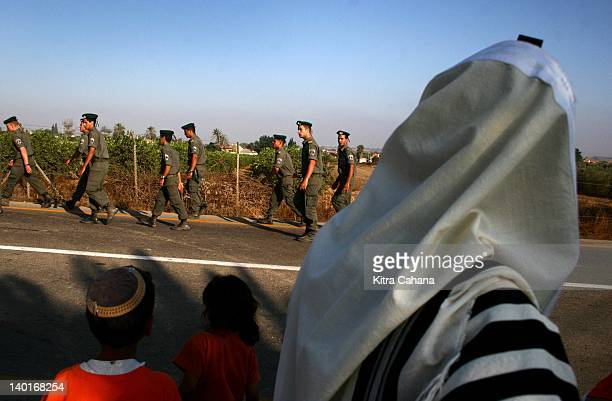 IDF soldiers walk past a religious Jewish man in the midst of the early morning prayer service near the Israeli village of Kfar Maimon on July 19...
