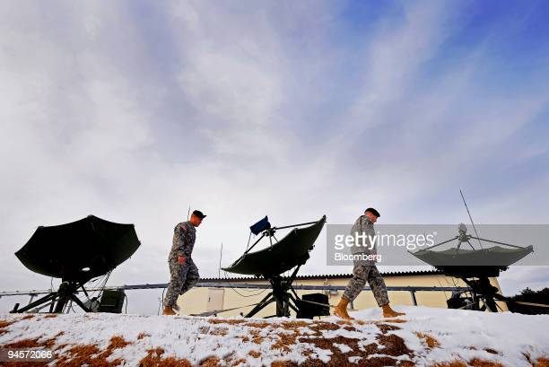 S soldiers walk past antennas used to pick up data at the Joint Tactical Ground Station which was formally unveiled at the Misawa Air Base in Aomori...